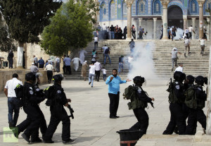 Muslim worshippers run as tear gas fired by Israeli policemen rises during clashes with stone-throwing Palestinian protesters in Jerusalem's Old City