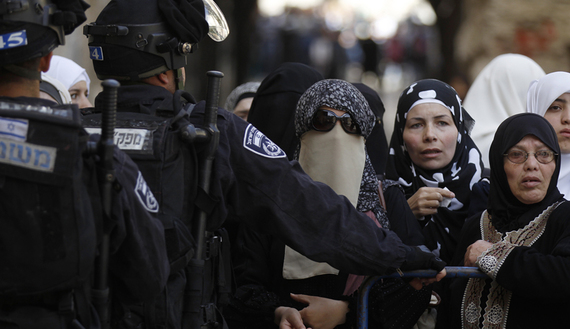 Israeli policemen prevent Palestinian women from entering the compound which houses al-Aqsa mosque in Jerusalem's Old City