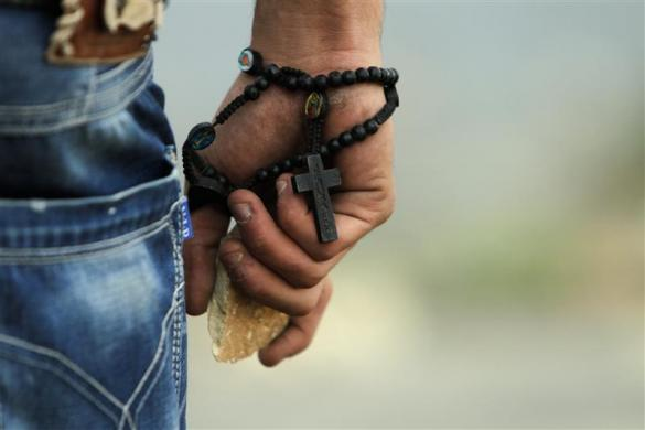 A Palestinian demonstrator wearing a rosary holds a stone during minor clashes with Israeli troops in protest against Israel's military operation in the Gaza Strip, in the West Bank village of Bir Zeit, near Ramallah