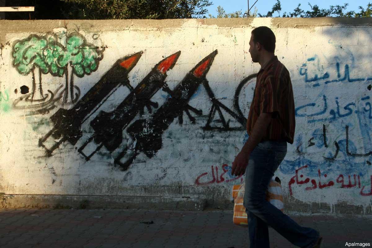 gaza-man-walks-past-images-of-gaza-palestinian-rockets