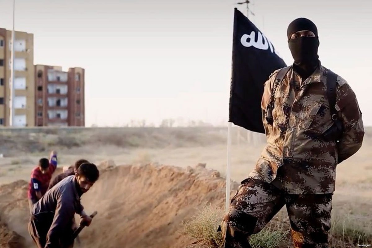 isis-soldier-posing-in-front-of-people-digging-their-own-graves
