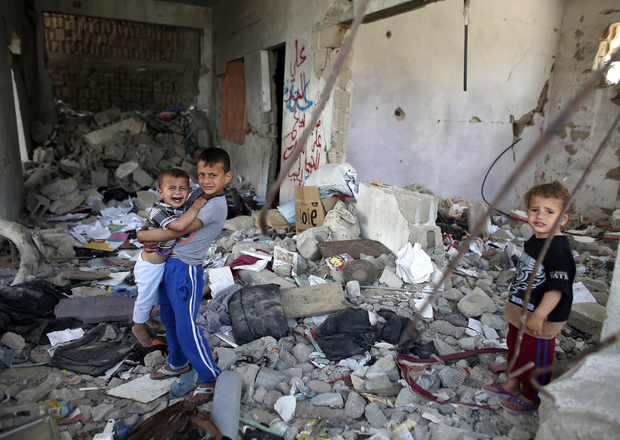 Palestinian children stand amid the rubble of their partially rebuilt house, on May 11, 2015, which was destroyed during the 50-day war between Israel and Hamas militants in the summer of 2014, in the Eastern Gaza City Shujaiya neighbourhood. AFP PHOTO / THOMAS COEX