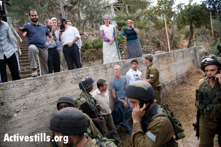 With Israelis from Tel Rumeida settlement looking on from above, Israeli soldiers arrest two Palestinians and an international volunteer after confrontations between settlers, the Al Azzeh family who had just harvested their olives, and the military, October 22, 2012. The arrests followed the first time the Al Azzeh family was able to harvest their olives since 2007. Despite coordinating with the appropriate authorities, their harvest was disrupted by Israelis from the adjacent Tel Rumeida settlement, which like all settlements, is illegal under international law.