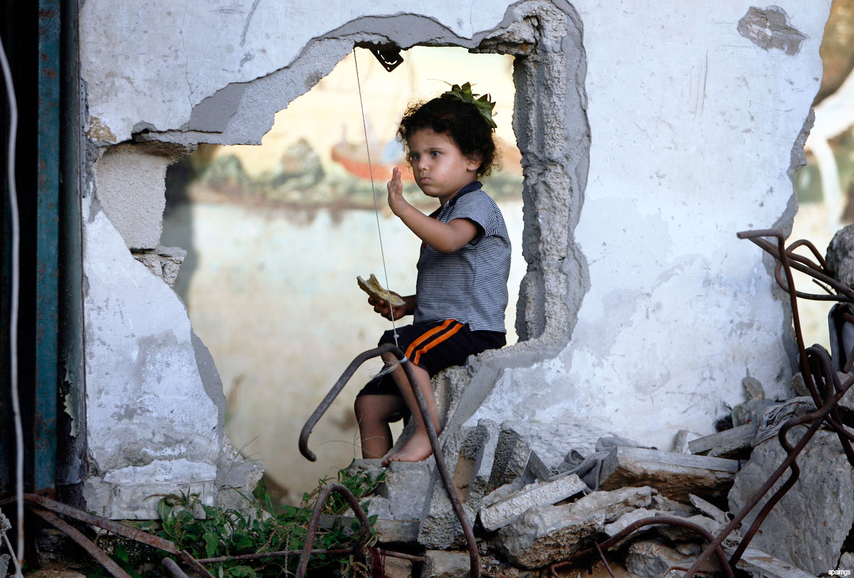 Palestinian-child-plays-in-her-destroyed-house