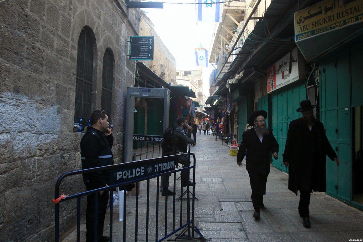 jewish-men-walk-past-store-in-Jerusalem-Old-City-taken-over-by-israeli-settlers-guarded-by-Israeli-police-Dec-2015