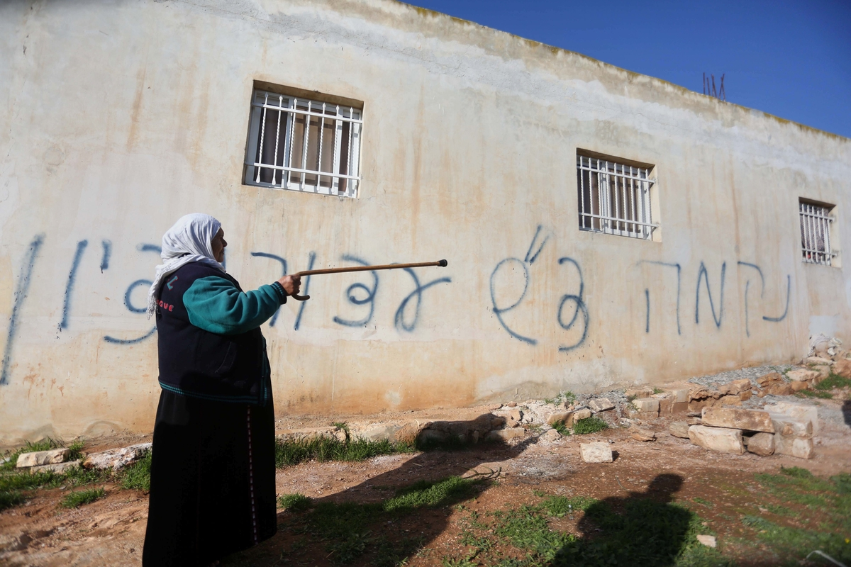 """A Palestinian woman stands next to a house sprayed with graffiti reading in Hebrew: """"revenge"""" and """"hello from the prisoners of Zion"""", in the village of Beitillu, near Ramallah in the Israeli occupied West Bank on December 22, 2015. Two tear gas canisters were also thrown into the Palestinian home by suspected Jewish extremists, Israeli police said, but the family there at the time was not hurt. Photo by Shadi Hatem"""