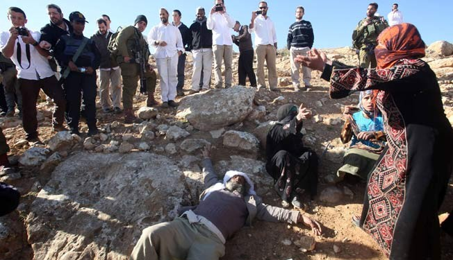 Israeli settlers, from the Maaon settlement, take pictures of an elderly Palestinian shepard after he was pushed on the ground near the village of Umm el-Kheir in the southern hills of the West Bank city of al-Khalil (Hebron) on January 25, 2014.