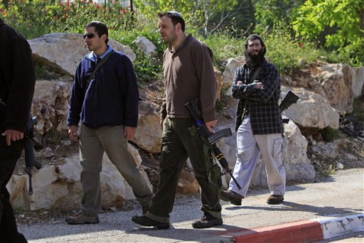 Armed Jewish settlers walk in the West Bank Jewish settlement of Beit Hagai after a Palestinian who infiltrated the settlement was killed by settlers Friday, April 17, 2009. A Palestinian wielding a knife was shot and killed by Jewish settlers early Friday when he tried to attack residents of a West Bank settlement, the Israeli military said, in violence likely to further heighten tensions between the Palestinians and Israel's new hard-line government. (AP Photo/Tsafrir Abayov)
