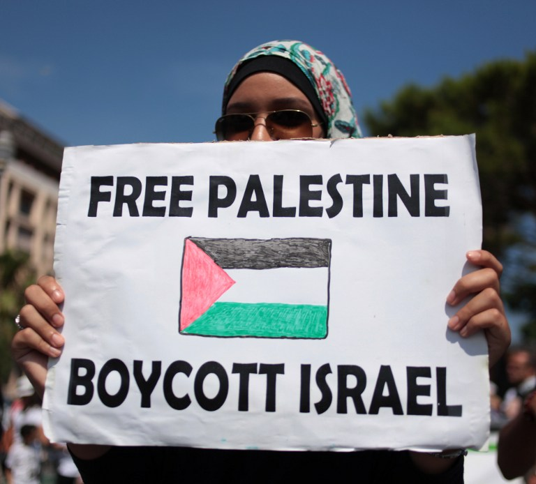 """A protester holds a placard reading """"Free Palestine, Boycott Israel"""" during a demonstration against Israel's military operation in Gaza and in support of the Palestinian people in Nice, southeastern France, on August 9, 2014. Israeli warplanes carried out 30 air strikes over Gaza on August 9, 2014, killing five Palestinians, as militants fired six rockets into Israel, leaving international mediators scrambling to rescue ceasefire talks. AFP PHOTO / JEAN-CHRISTOPHE MAGNENET"""